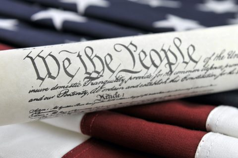 Photo: U.S. Constitution and American Flag | Credit: Justasc, YFS Magazine, Adobe Stock