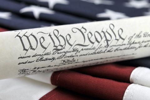 Photo: U.S. Constitution and American Flag | Credit: Justasc, YFS Magazine, Adobe Stock